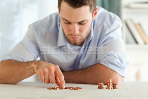 Young businessman counting his small coins Stock photo © wavebreak_media