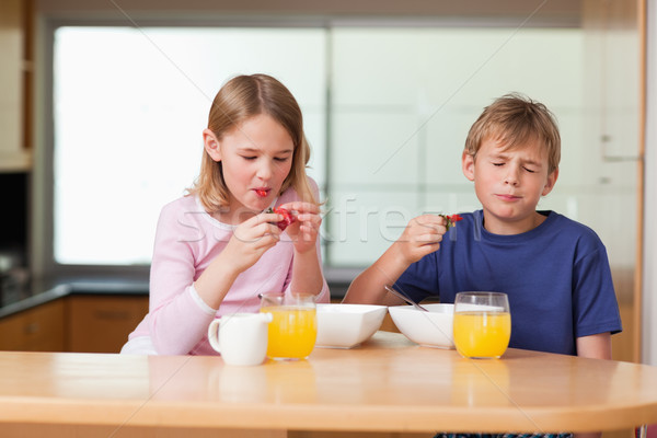 Siblings eating strawberries for breakfast in a kitchen Stock photo © wavebreak_media