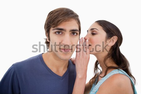 Stock photo: Woman whispering something to her fiance against a white background