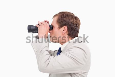 Side view of businessman using spy glasses against a white background Stock photo © wavebreak_media