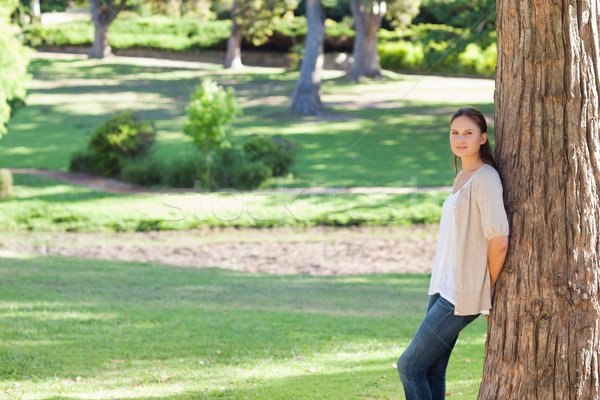 Woman leaning against a tree in the park Stock photo © wavebreak_media