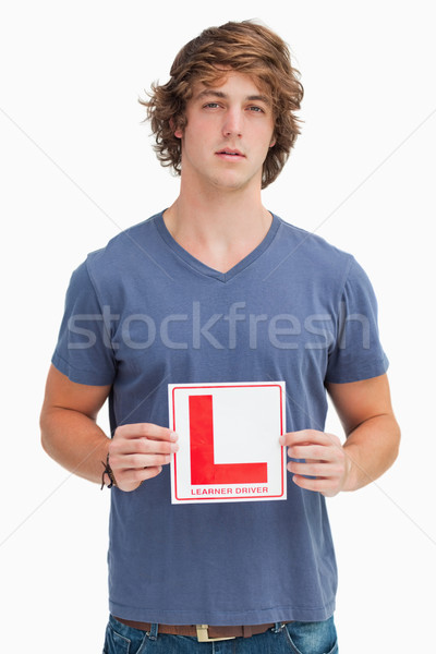 Young man holding a learner driver sign against white background Stock photo © wavebreak_media