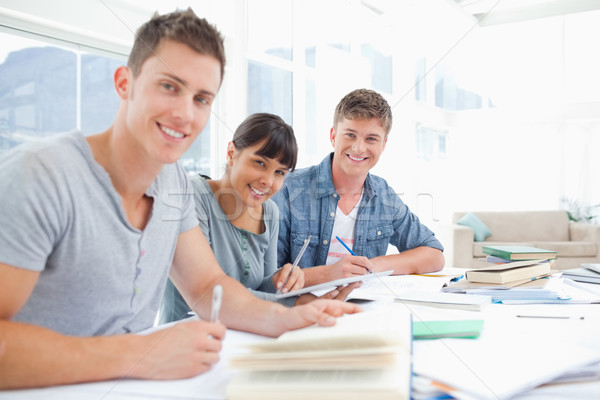 A group of smiling students look into the camera as they all do homework Stock photo © wavebreak_media