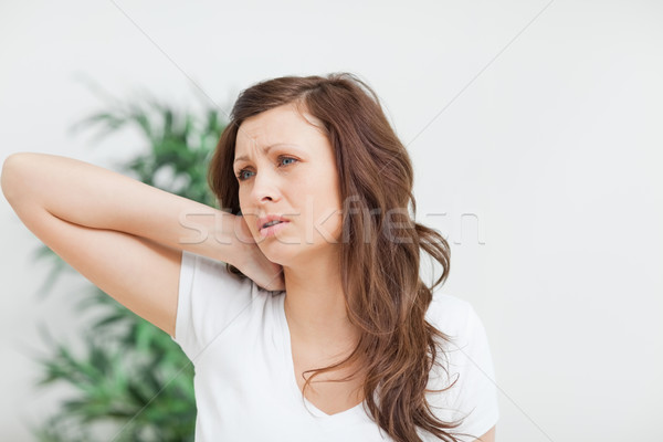 Woman placing her hand on her neck in a room Stock photo © wavebreak_media