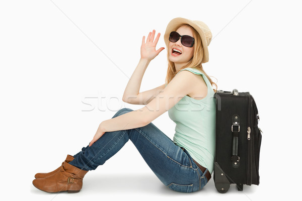 Stock photo: Woman raising her hand while sitting next to a suitcase against white background