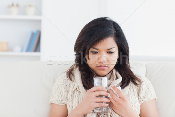 Stock photo: Woman holding a glass of water while being cold in a living room