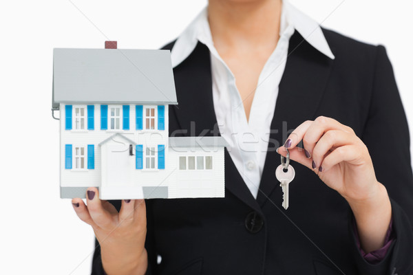 Businesswoman in suit holding a model house and key Stock photo © wavebreak_media