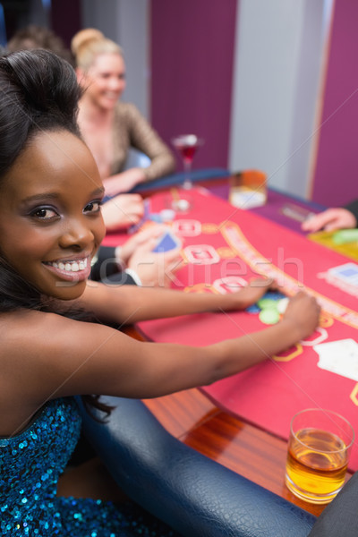 Woman smiling grabbing chips at the casino table Stock photo © wavebreak_media