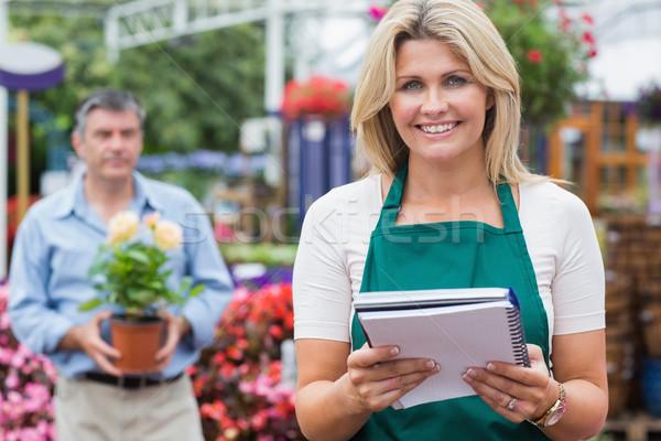 Uśmiechnięta kobieta notatnika roślin ogród centrum Zdjęcia stock © wavebreak_media