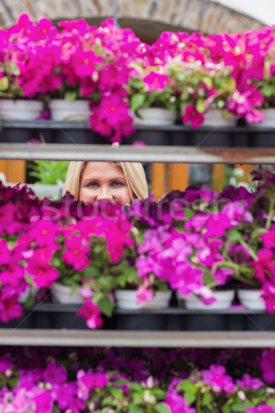 Woman looking through shelves in flowers store while smiling Stock photo © wavebreak_media