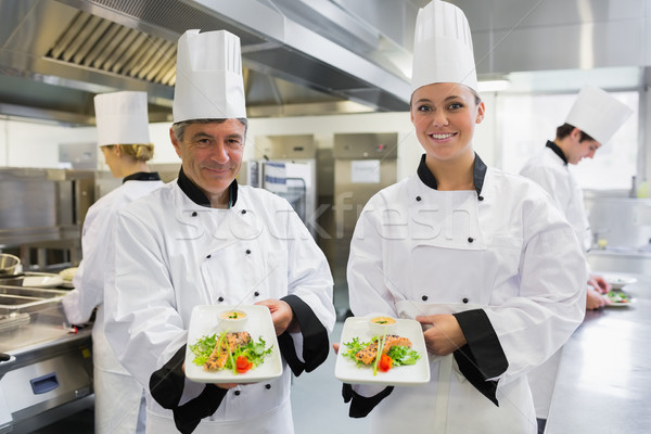 Two Chef's showing salmon dishes in the kitchen Stock photo © wavebreak_media