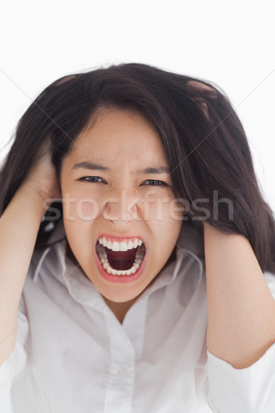 Screaming brunette pulling her hair on white background Stock photo © wavebreak_media