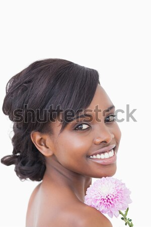 Pretty woman holding a pink coloured flower while smiling against white background Stock photo © wavebreak_media