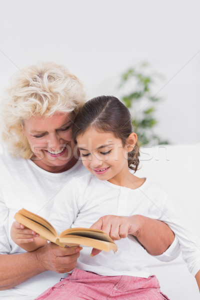 Cheerful granddaughter and grandmother reading a novel together Stock photo © wavebreak_media