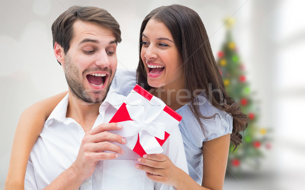 Composite image of woman surprising boyfriend with gift Stock photo © wavebreak_media