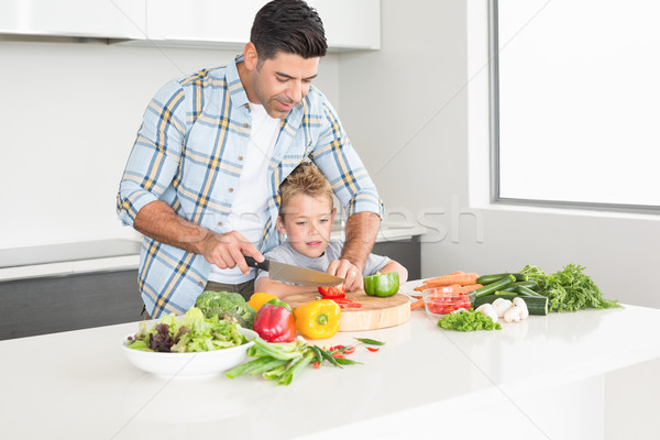 Father teaching his son how to chop vegetables Stock photo © wavebreak_media