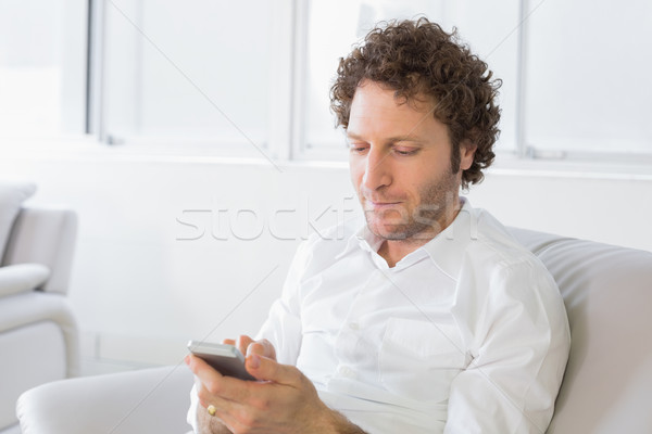 Relaxed man text messaging at home Stock photo © wavebreak_media