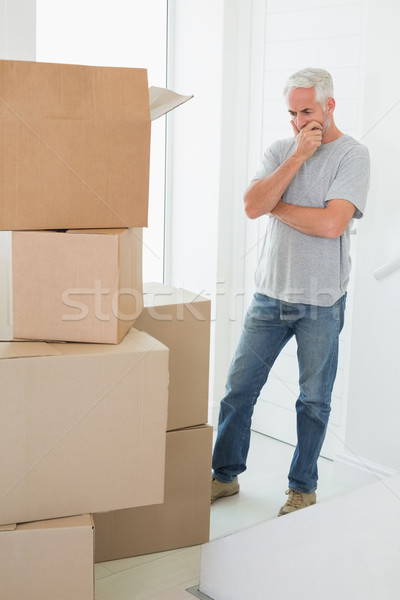 Thoughtful man looking at cardboard moving boxes Stock photo © wavebreak_media