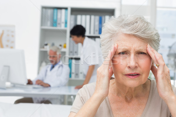 Senior patient suffering from headache with doctors at medical o Stock photo © wavebreak_media