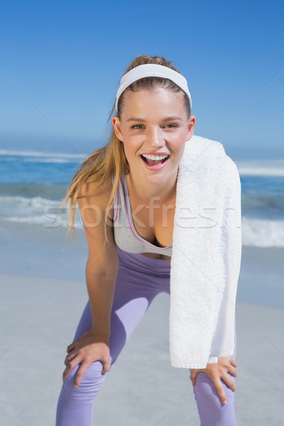 Sporty smiling blonde standing on the beach with towel Stock photo © wavebreak_media