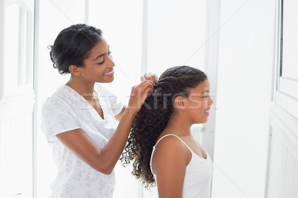 Pretty mother tying her daughters hair back Stock photo © wavebreak_media