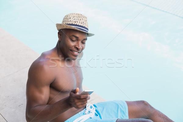 Handsome shirtless man texting on phone poolside Stock photo © wavebreak_media