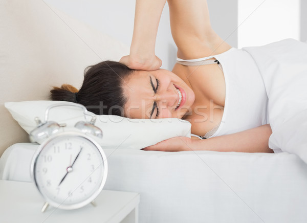 álmos nő fül kéz ágy ébresztőóra Stock fotó © wavebreak_media