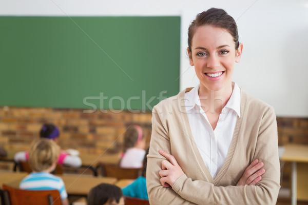 Pretty teacher smiling at camera at back of classroom Stock photo © wavebreak_media