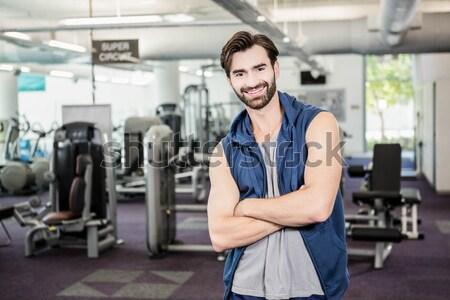 Handsome man smiling at camera beside treadmills Stock photo © wavebreak_media