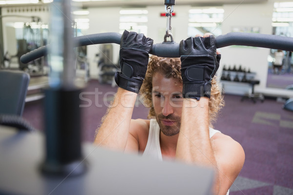 Young man exercising on a lat machine in gym Stock photo © wavebreak_media