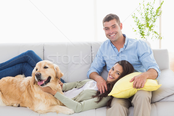 Happy couple with dog relaxing on sofa Stock photo © wavebreak_media