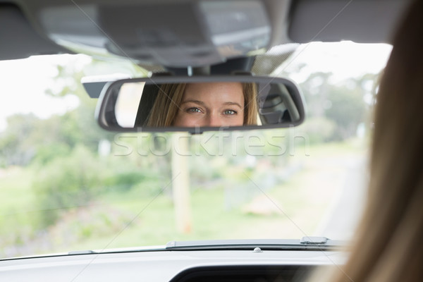 Young woman in the drivers seat looking in the mirror Stock photo © wavebreak_media