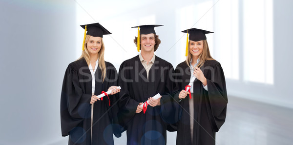 Composite image of three students in graduate robe holding a dip Stock photo © wavebreak_media