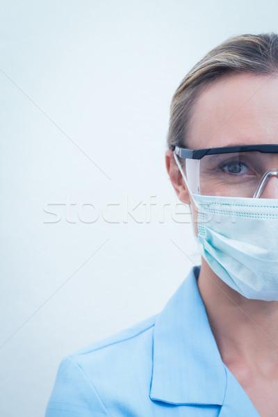 Female dentist wearing surgical mask and safety glasses Stock photo © wavebreak_media