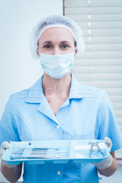 Female dentist in surgical mask holding tray of tools Stock photo © wavebreak_media