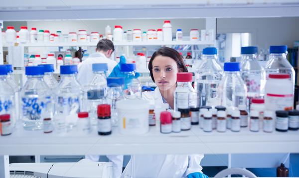 Jovem químico para cima garrafas prateleira Foto stock © wavebreak_media