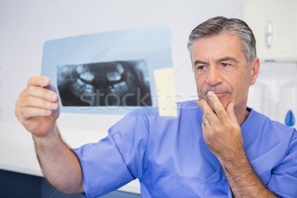 Thoughtful dentist studying x-ray attentively Stock photo © wavebreak_media