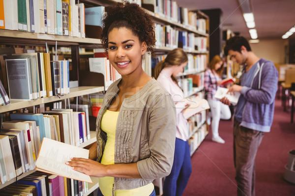 Happy student taking book from shelf Stock photo © wavebreak_media