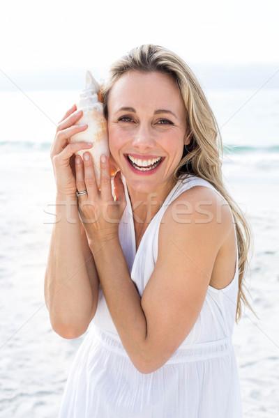 Smiling blonde in white dress listening the seashell Stock photo © wavebreak_media