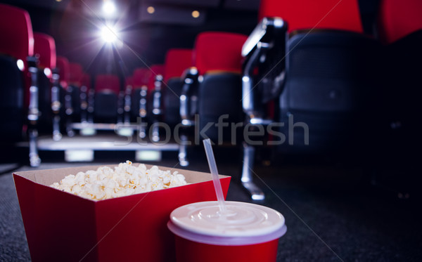 Stock photo: Empty rows of red seats with pop corn and drink on the floor