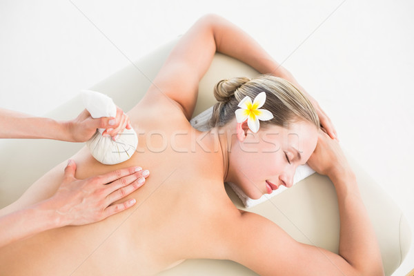 Beautiful blonde enjoying a herbal compress massage Stock photo © wavebreak_media