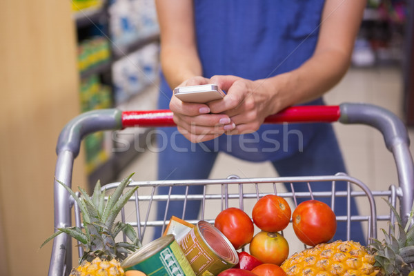 Woman pushing trolley in aisle and texting  Stock photo © wavebreak_media