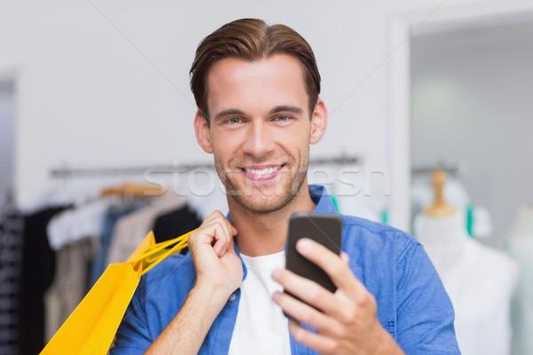 ストックフォト: 笑みを浮かべて · 男 · ショッピングバッグ · 見える · スマートフォン · 服