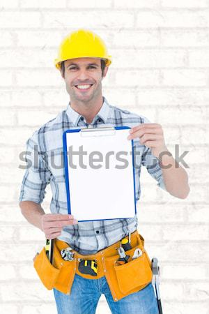 Composite image of portrait of smiling handyman holding toolbox Stock photo © wavebreak_media