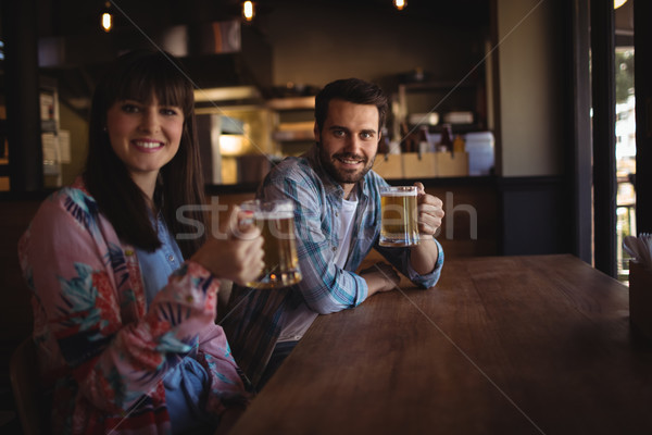 Portrait of happy couple holding glasses of beer at counter Stock photo © wavebreak_media