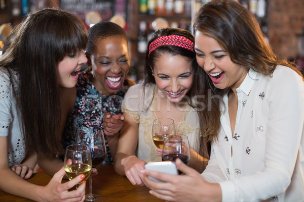 Stock photo: Happy female friends with wineglasses using mobile phone