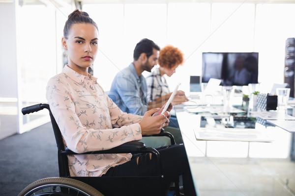 Portrait of businesswoman using digital tablet while sitting on wheelchair Stock photo © wavebreak_media