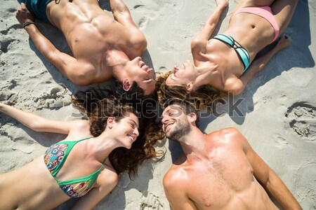 Overhead view of young couple lying together on sand at beach Stock photo © wavebreak_media