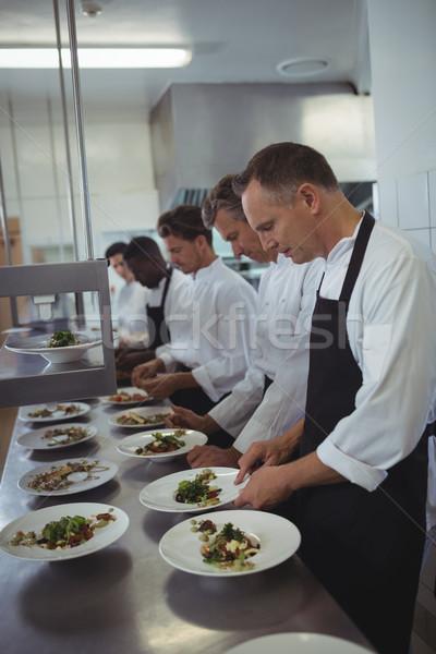 Team of chefs garnishing meal on counter Stock photo © wavebreak_media