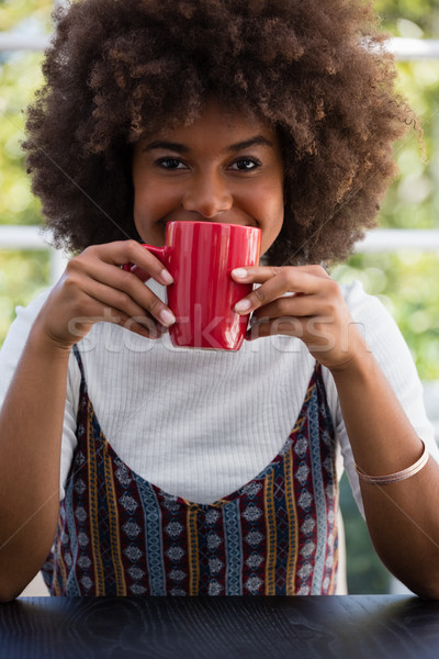 Smiling woman with frizzy hair having coffee in cafe Stock photo © wavebreak_media